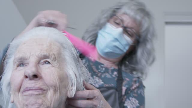 冷たく、インフルエンザの季節にcovid sars ncov 19コロナウイルス豚インフルエンザh7n9インフルエンザの広がりを防ぐために、青いフェイスマスクを着用したプロの介護者スタイリストによって - 髪をブラシでとく点の映像素材/bロール