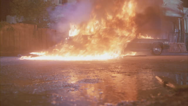 Close-up shot of a car exploding on a street.