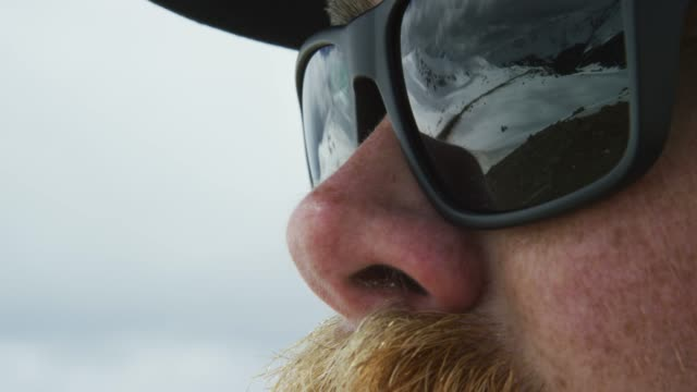 nahaufnahme eines kaukasischen mannes in seinen zwanziger jahren mit einem mustache mit den snowy rocky mountains von colorado in der reflection seiner sonnenbrille - land stock-videos und b-roll-filmmaterial