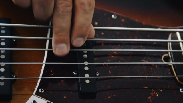 close-up shot of a caucasian man's fingers plucking the strings on a five-string electric bass guitar - bass guitar stock videos & royalty-free footage