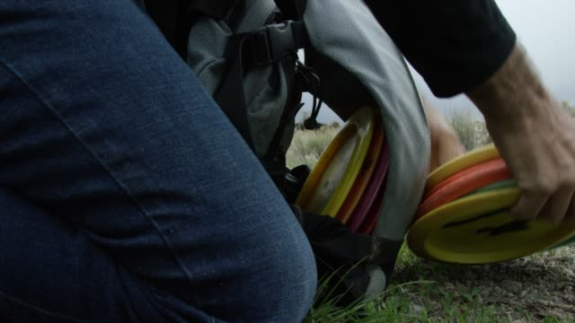 Close-Up Shot of a Caucasian Man's Hands Picking Up Disc Golf Discs off the Ground and Placing Them Into a Disc Golf Bag