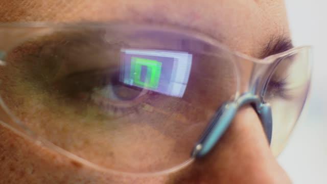 nahaufnahme eines kaukasischen technikers auge mit der reflexion eines computerbildschirms in seiner schutzbrille in einem innenministerium - schutzbrille stock-videos und b-roll-filmmaterial