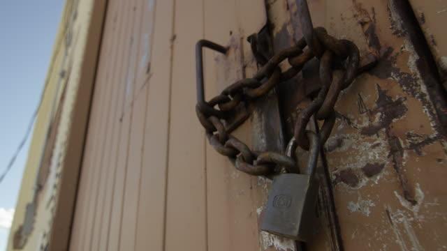 vidéos et rushes de close-up shot of a chained door moved by the wind at nevada test site - arme de destruction massive