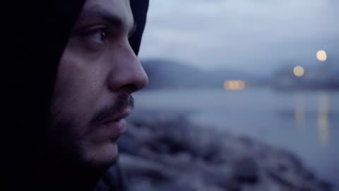 vídeos y material grabado en eventos de stock de primer disparo de un hombre angustiado en lago orilla contemplando y fumar cigarrillo - esconder