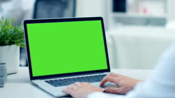 Close-up Shot of a Doctor Working on a Laptop with Green Screen On. His Colleague in the Background. Office is Modern and Well Lit.