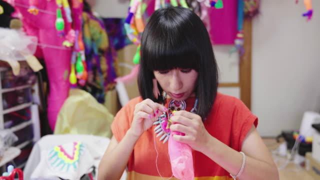 nahaufnahme einer künstlerin beim nähen in ihrem eklektischen kunstatelier - einzelne frau über 30 stock-videos und b-roll-filmmaterial
