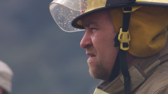 Close-up shot of a fireman as he surveys the scene and whistles