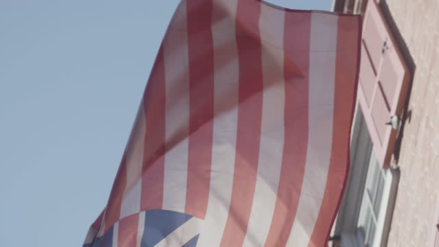 close-up shot of a grand union flag waving in the elfreths alley street - union jack stock videos & royalty-free footage