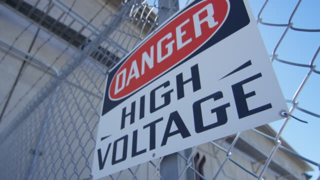 close-up shot of a high voltage sign at nevada test site - recinzione video stock e b–roll