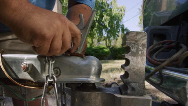 close-up shot of a hispanic man's hands attach a trailer coupler with a latch to the ball hitch on his vehicle on a sunny day - machine part stock videos & royalty-free footage