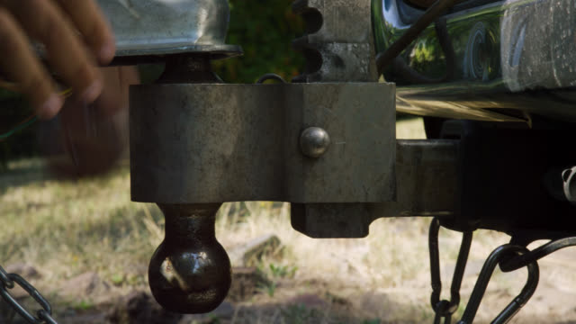 close-up shot of a hispanic man's hands closing the latch on the trailer coupler, attaching the safety chains, and installing the coupler pin before hooking up the electrical to his vehicle on a sunny day - towing stock videos & royalty-free footage