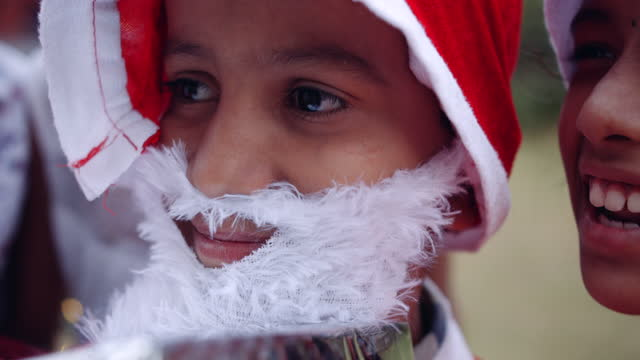 closeup shot of a kid dressed as santa handheld as his sister says something whispers in his ears as they fun and everyone seems to have a great time - weihnachtsmütze stock-videos und b-roll-filmmaterial