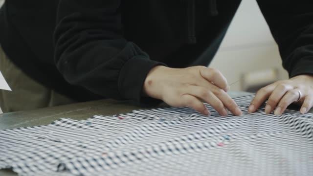 vídeos de stock e filmes b-roll de close-up shot of a mid adult textile artist working in her design studio - textile factory