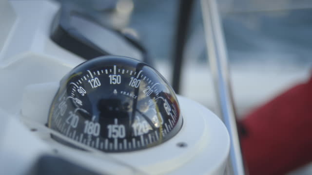 close-up shot of a modern nautical compass and hands steering a boat, uk. - sailing stock videos & royalty-free footage