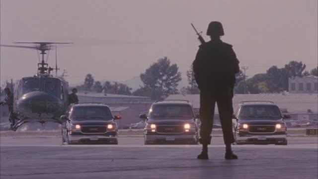 vídeos y material grabado en eventos de stock de close-up shot of a motorcade moving towards a soldier. - carro blindado