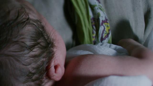 vidéos et rushes de close-up shot of a newborn baby held by a woman - image du xviiième siècle
