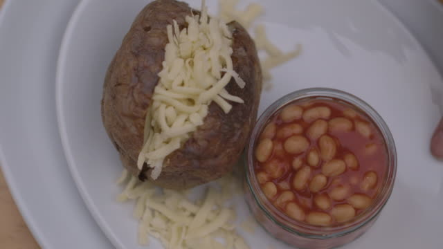 close-up shot of a plate of baked beans and a cheese-filled baked potato being moved on a tabletop, uk. - bean stock videos and b-roll footage