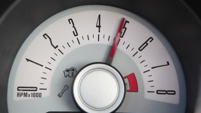 Close-up shot of a rev counter reaching the numbers four, six and seven on an American car (with sound).