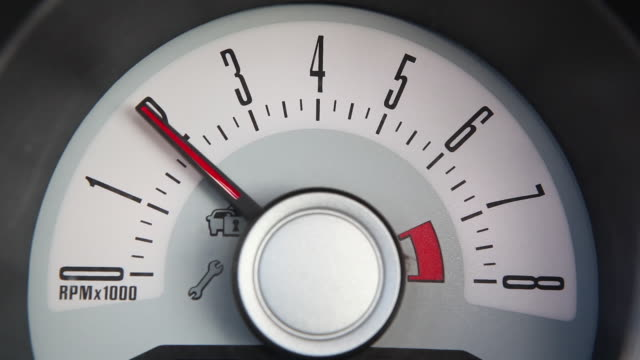 Close-up shot of a rev counter reaching the numbers two and six on an American car.