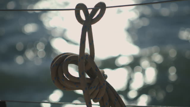 Close-up shot of a rope tied into a nautical knot on a moving yacht, UK.