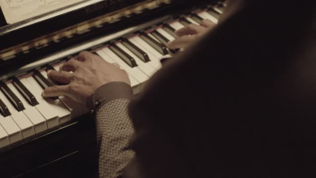 Close-up shot of a senior African-American pianist playing the piano