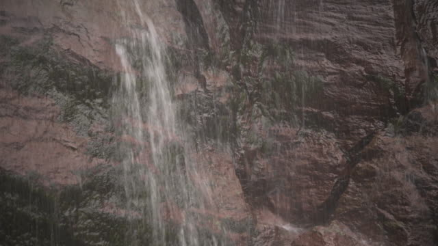Close-up shot of a sheet of gushing water of the Kaaterskill Falls running over mossy rocks, Catskill Mountains, New York State, USA.