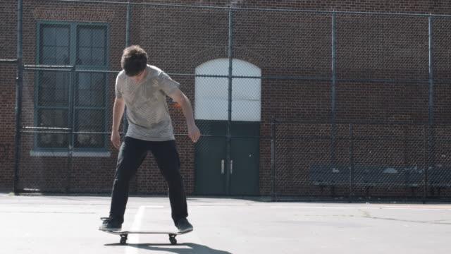 a closeup shot of a skateboarding falling on a spring day in brooklyn, nyc - fence点の映像素材/bロール