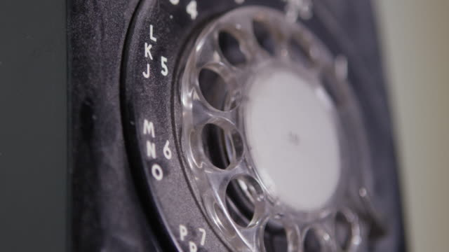 close-up shot of a vintage rotary telephone while a person is dialing a number at nevada test site - disco combinatore video stock e b–roll