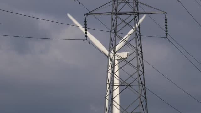 close-up shot of a wind turbine on ince salt marshes seen behind an electricity pylon on november 7, 2016 in runcorn, england. - hochspannungsmast stock-videos und b-roll-filmmaterial