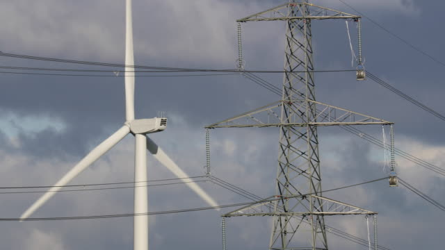 close-up shot of a wind turbine on ince salt marshes standing near to an electricity pylon on november 7, 2016 in runcorn, england. - hochspannungsmast stock-videos und b-roll-filmmaterial