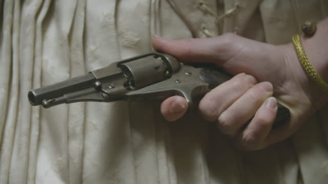 close-up shot of a woman in costume holding a gun behind her back - gripping stock videos & royalty-free footage