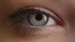 Close-up shot of a woman opening her blue eyes with light day make-up and focusing them.