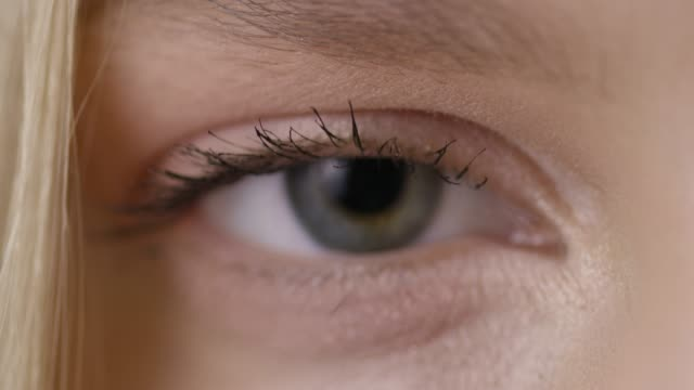 Close-up shot of a woman opening her eyes with light day make-up