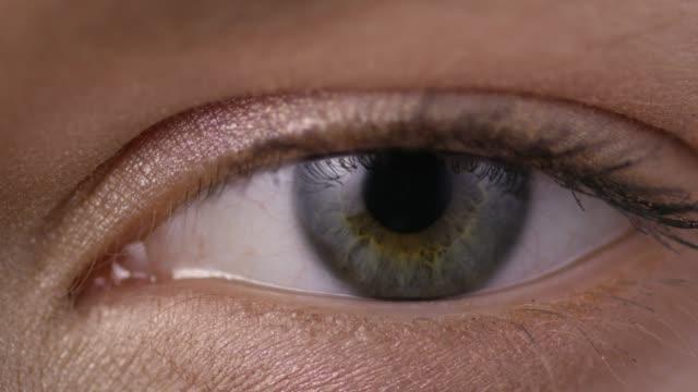 stockvideo's en b-roll-footage met close-up shot van een vrouw die haar ogen openen met lichte dag make-up - netvlies