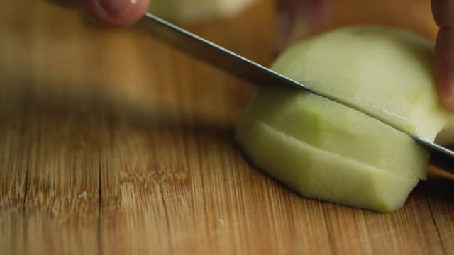 close-up shot of a woman's hands cutting a peeled apple into slices on a wooden cutting board with a kitchen knife - apple fruit stock videos & royalty-free footage