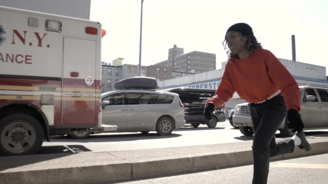 A closeup shot of a young, black woman skateboarding through the streets of Brooklyn, New York City - 4k