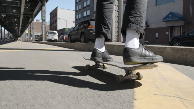 a closeup shot of a young, black woman skateboarding through the streets of brooklyn, new york city - 4k - human limb stock videos & royalty-free footage