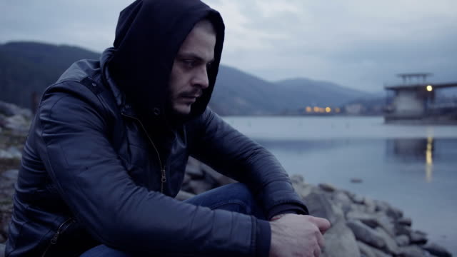 Close-up shot of a young depressed man sitting on lake shore and contemplating