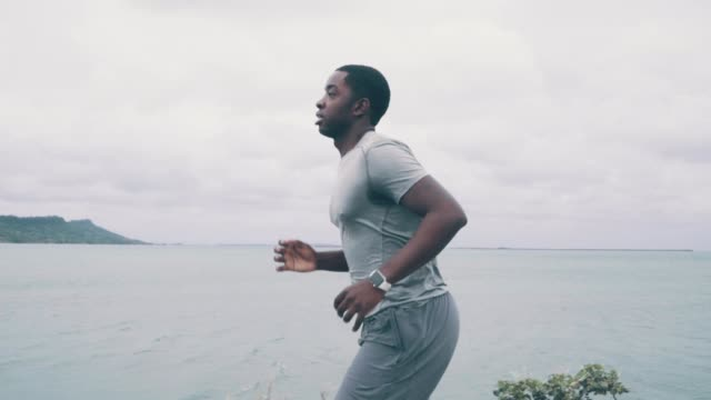 close-up shot of a young man jogging along the coast in the morning - african american ethnicity stock videos & royalty-free footage