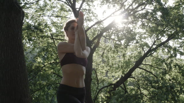 Closeup shot of a young woman practicing Yoga at sunrise - 4k - slow motion