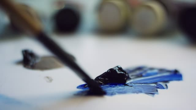close-up shot of an artist spreading blue oil paint around a canvas with a brush - oil paint stock videos and b-roll footage