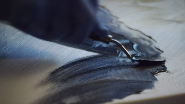 close-up shot of an artist wearing protective gloves applying oil paint to a canvas using a palette knife - oil paint stock videos & royalty-free footage