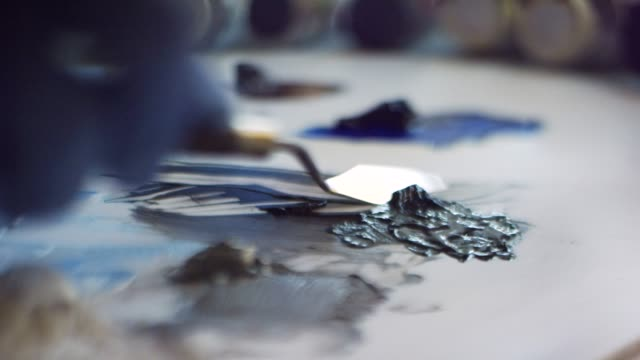 close-up shot of an artist wearing protective gloves spreading oil paint around a canvas with a palette knife - art studio stock videos & royalty-free footage