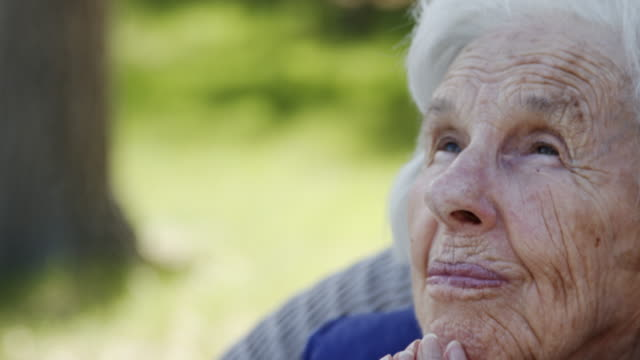 close-up shot of an elderly senior caucasian christian woman with folded hands looking up praying in a lawn chair outdoors in the summer - hands clasped stock videos & royalty-free footage