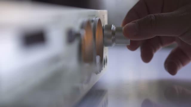 stockvideo's en b-roll-footage met close-up shot van een oude versterker knop, terwijl een man schakelen een wijzerplaat in 4k-resolutie. - stereo