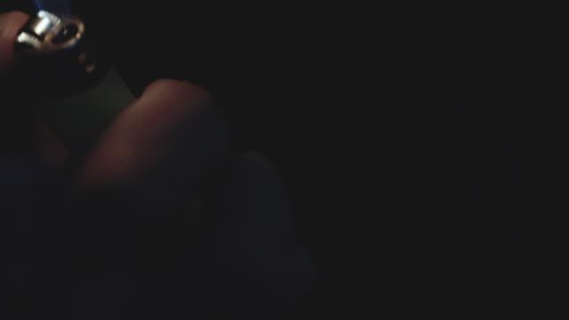 A closeup shot of an unrecognizable Caucasian Man lighting a lighter in the dark.