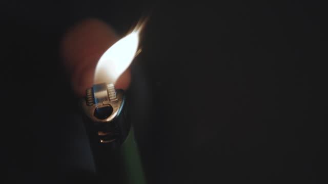 a closeup shot of an unrecognizable man sparking a lighter in the dark - 4k - feuerzeug stock-videos und b-roll-filmmaterial