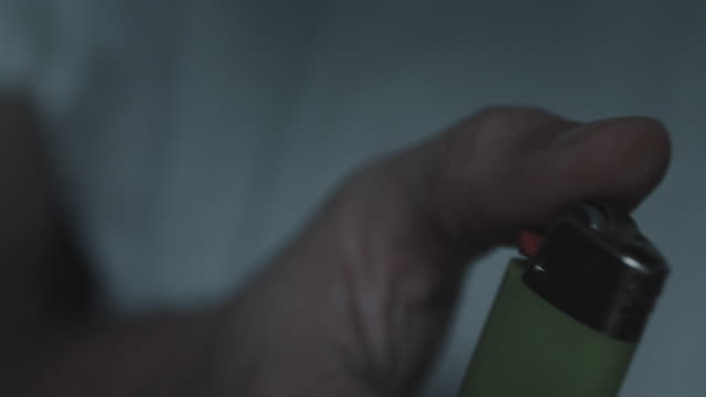 A closeup shot of an unrecognizable man sparking a lighter in the dark - 4k