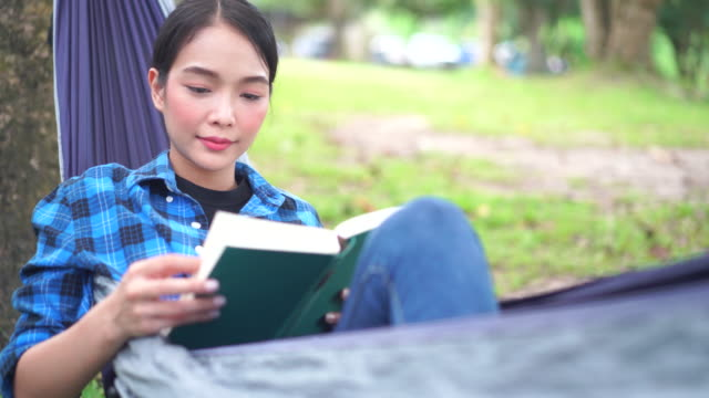 close-up shot of asian woman relaxing in a hammock reading a book at campground - 読む点の映像素材/bロール