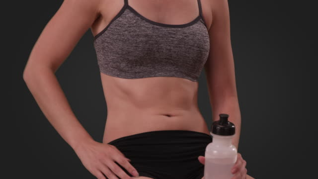 close-up shot of athletic fit white female's body on gray background - sports bra stock videos & royalty-free footage